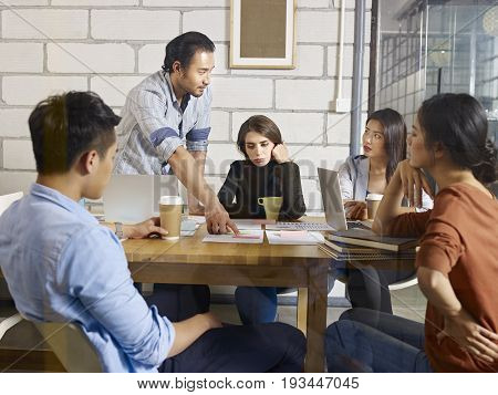 a team of multinational corporate people discussing business in glass meeting room.