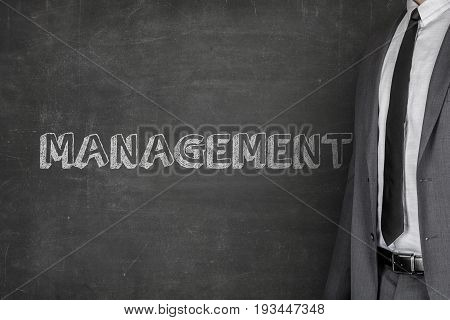 Midsection of businessman standing by management text on blackboard