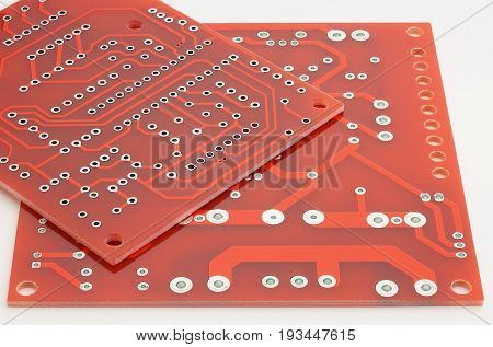 New printed circuit boards without electronic components on a white background.