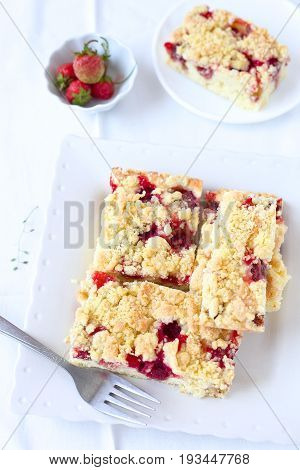 Homemade crumble cake with strawberries on a white plate.