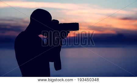Photographer taking pictures outdoors, silhouette of a man with camera over sunset background, photographing beautiful view of wild nature