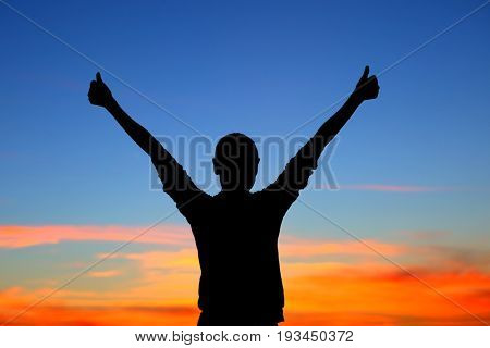 Silhouette of a happy woman with raised up hands on beautiful colorful sunset background, enjoying life and showing good mood, happy summer holidays