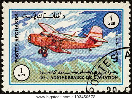 Moscow Russia - April 14 2017: A stamp printed in Afghanistan shows old flying aircraft (biplane) over mountains series