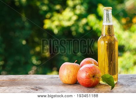 cold apple cider in glass bottle and ripe fresh apples on wooden table on nature background. Refreshing summer drink