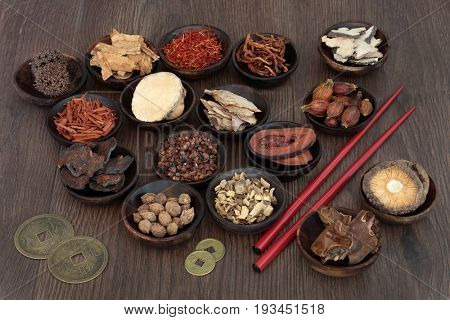 Chinese herbal medicine selection in wooden bowls with feng shui coins and chopsticks on oak background.