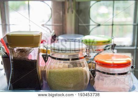 A jar of creamer sugar coffee on a plastic tray.