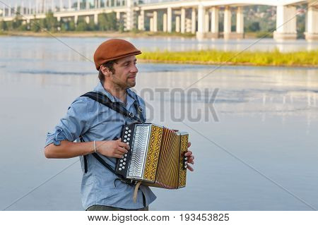 French man playing accordion in the evening by the river bank