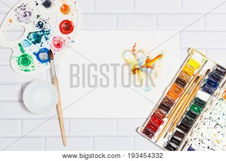Hand Drawn Sketch of Watercolor Orange Dragonfly, with lying paints, paintbrushes and palette on the white brick background - concept of human creativity, top flat view. Central empty place for text