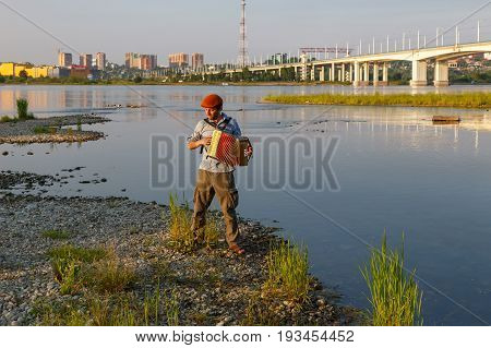 Man in hat playing accordion at the river side in Irkutsk in the evening