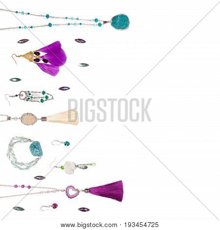 Handmade turquoise and violet bijouterie with gems, tassels and feathers, lying flat on the white square background with empty place for text, top view