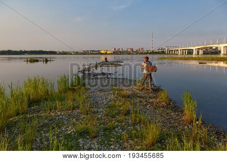 Evening view of Irkutsk city with bridge and river and man playing accordion
