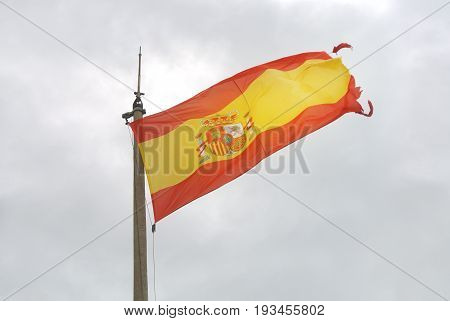 Old Spanish flag on a pole undulating in the wind with clouds at the background Santa Barbara castle of Alicante Spain.