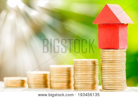 home model pot on golden collect coins with green nature blurred background and sunlight