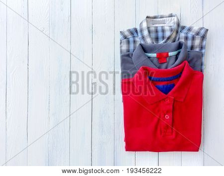 Top view of man polo shirt put on white wooden background