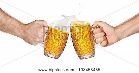two mugs of beer toasting creating splash isolated on white background. Pair of male hands holding beer mugs making toast. Beer up