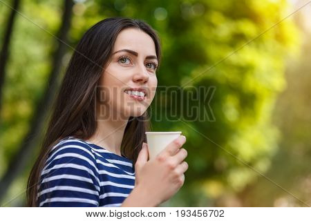 portrait of happy girl in summer park. Beautiful young brunette woman holding disposable cup of coffee outdoors. Morning coffee