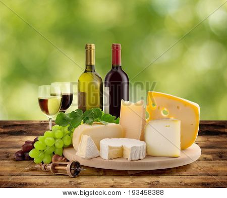 cheeseboard grape and wine on wooden table in countryside