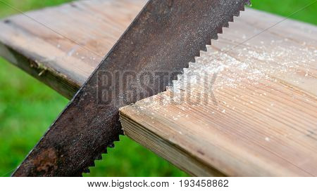 An old saw cuts a wooden board