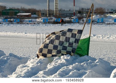 Starting judicial flags stuck in the snow on the speedway sports track