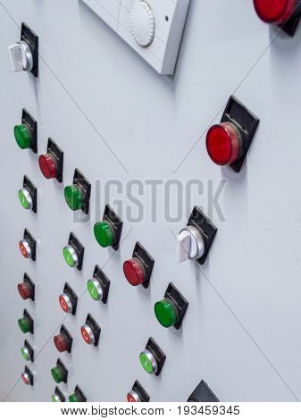 Close Up of lit lights and control colorful buttons on industrial manufacturing machinery