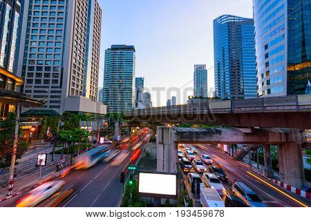 Photo of commercial office buildings exterior. Night view at bottom skyscrapers with blank bill board and light of traffic rush in Bangkok.