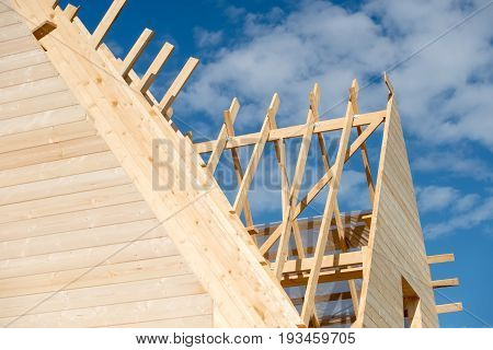 The rafters of the roof of the new wooden house under construction