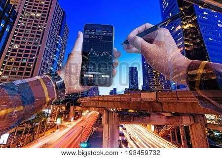 Double exposure of hands in hipster shirts holding smart phone for check stock market graph withlight of night building background Business Trading concept.