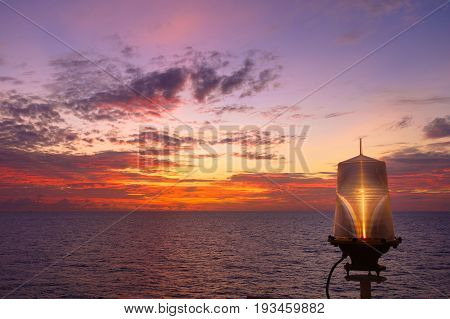 Fiery orange sunset sky warm light with clouds on the sea Beautiful for background with nav aids lamp on offshore oil and gas platform.