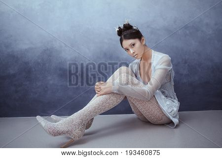 Futuristic fashion young woman. Beautiful young multi-racial asian caucasian model cyber girl in silver urban clothes with conceptual hairstyle and make-up sitting against textured blue wall in full lenght. Sci-fi poster style.