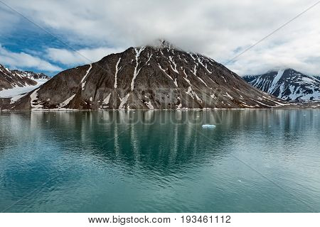 Clouds over the mountains along the Magdalenafjord in Svalbard islands Norway