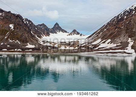 Snowy mountains along the Magdalenafjord in Svalbard islands Norway