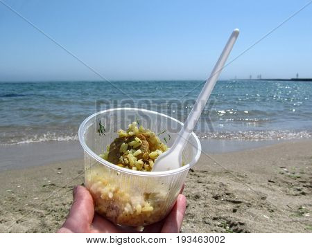 Rice with meat close-up on the sea shore. A female hand holds a takeaway food in a plastic disposable tableware on the beach. Concept of fast food takeaway