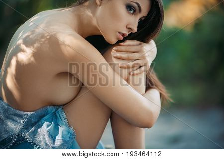 Lonely Girl in Love. Fashion Art Photo. Sexy attractive Woman with naked breast and back sitting and ambracing her knees. Beautiful creative close-up portrait shot of sensual seductive multi-racial Asian Caucasian female model in shadow of trees. Our thou