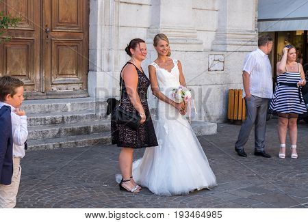 The Bride And Her Friend Posing Near A Church In Annecy,  France