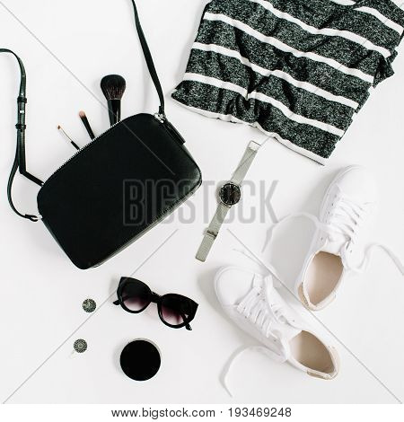 Trendy fashion black styled woman clothes and accessories collection on white background. Flat lay top view. Sneakers watches sunglasses t-shirt purse.