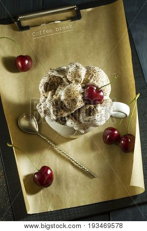 Chocolate cake with cherries and a cup of coffee with whipped cream. Coffee break. Wooden dark blue background