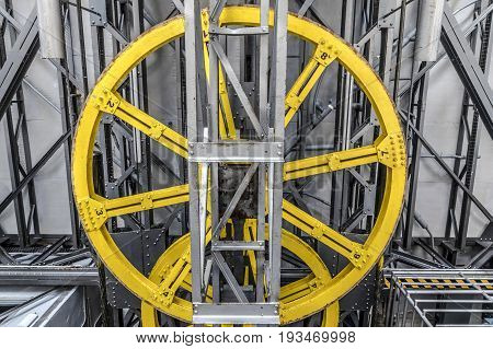 Yellow machinery wheel with metal silver construction pieces and cables at Barcelona's port cable car
