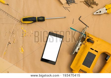 Carpenter handyman workshop desk tabletop with smart phone screen as copy space and tools