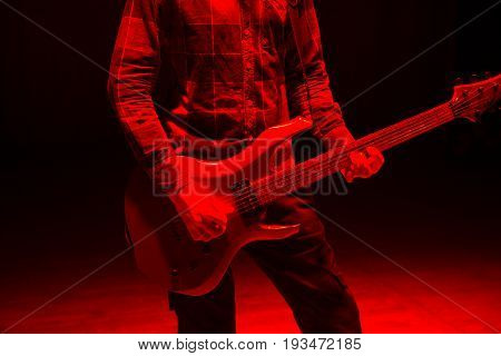 Hands Of Man Playing Electric Guitar In Red Light. Bend Technique