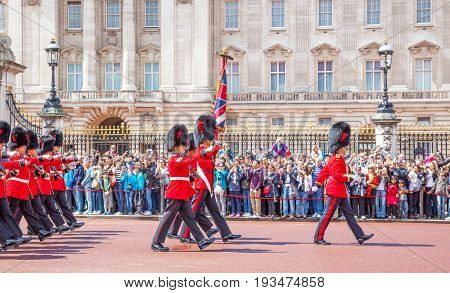 LONDON, UNITED KINGDOM - JULY 11, 2012: An officer and soldiers of the Coldstream Guards march past the front of Buckingham Palace during the Changing of the Guard ceremony.