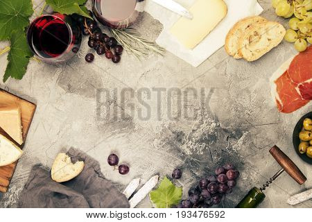 Wine and snack set. Variety of cheese, olives, prosciutto meat, baguette slices, black grapes and glasses of red wine over grey marble background, top view, copy space