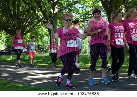 SOUTHAMPTON UK - July 2 2017: Race for Life women and men run and walk to raise money for Cancer Research charity in Southampton UK. Older women dressed up.