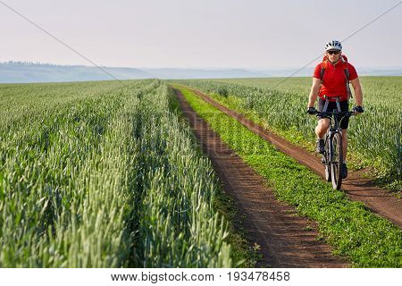 Young cyclist riding bicycle on the road on green field. Attractive sportsman in the sportwear, with backpack and helmet. Travel in the countryside. Horizontal photo