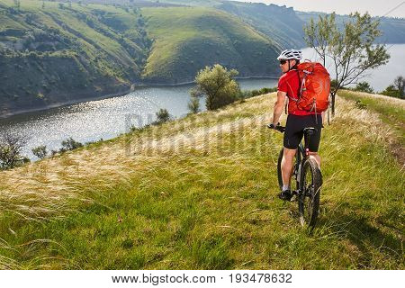 Adventure mountain biking on riverside. Traveler with backpack rides his bike in mountains.