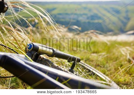 Close-up of detail of the mountain bicycle on the green grass. Helm and wheel of the bicycle. Horizontal photo. Sportive backgrounds. Extreme travelling in the countryside. Concept of the healthy and active lifestyle.