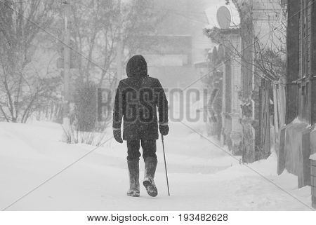 Lonely elderly man with a cane walking leisurely through a snow storm through the streets of the city.