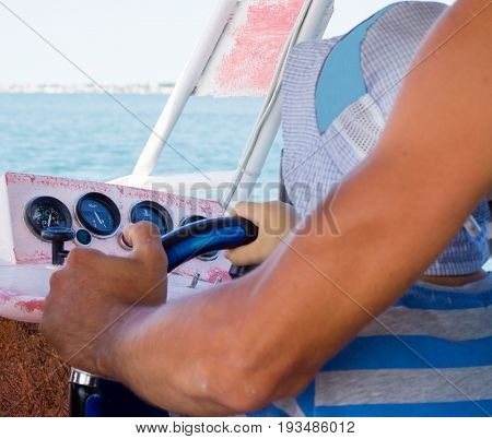 A little boy driving a boat he sits on his knees at the captain looks at the sea and clings to the wheel