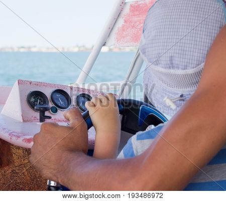 The hands of a small boy and a captain on the steering wheel of a boat sailing on the sea summer vacation