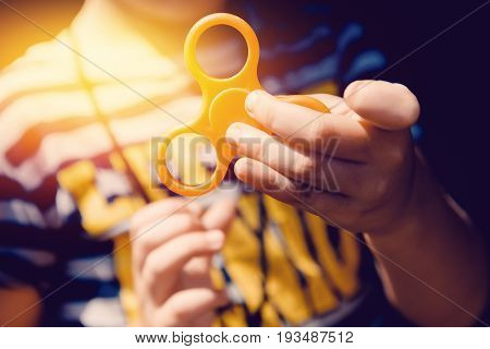 Child boy to play with Fidget Spinner in his hands the concept of relieving stress develop a small hand mathematics.