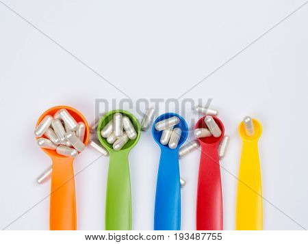 White Capsules Pills Spilling Out Of The Colorful Measuring Spoon On White Background. Increase The